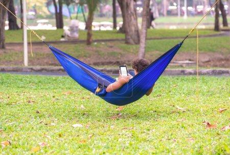 Photo pour Homme couché sur hamac dans le jardin avec tablette . - image libre de droit