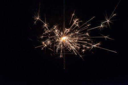 Photo pour Main tenant un feu scintillant sur fond noir . - image libre de droit