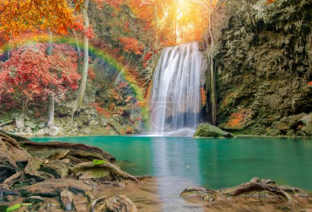 Wonderful Waterfall with rainbows and red leaf in Deep forest at