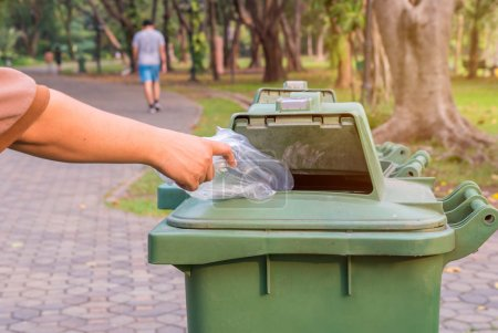 Photo for Hand throwing bottle in a trash cans. - Royalty Free Image