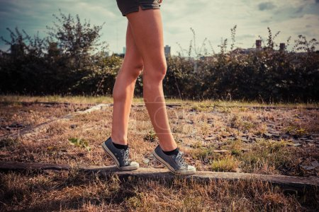 Photo for A young woman is walking on her tip toes on a wooden beam on the ground - Royalty Free Image
