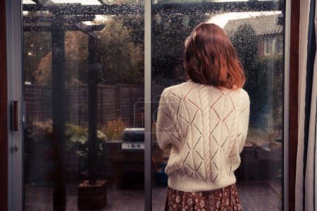 Young woman by window looking at the rain