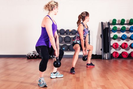 Two young women are working out with kettle bells ...