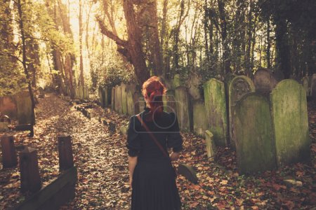 Woman walking amongst tombstones