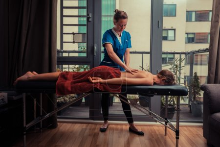 Photo for A massage therapist is treating a female client on a table in an apartment - Royalty Free Image