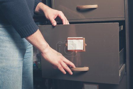A young man is opening a file cabinet...