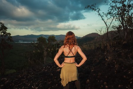 A young woman is standing on a hill scorched by a ...
