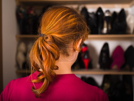 Photo for A young woman is organizing her shoe cupboard at home - Royalty Free Image