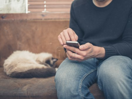 Photo for A young man is sitting on an old sofa with a cat sleeping next to him as he is using his smartphone - Royalty Free Image