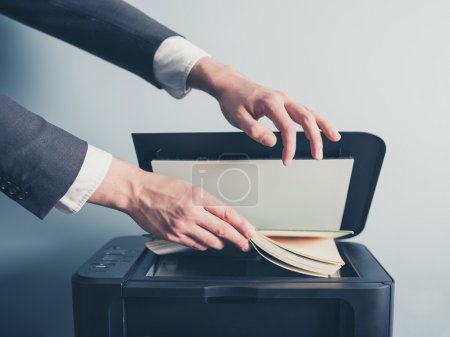 Young businessman photo copying a book