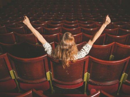 Excited woman in auditorium