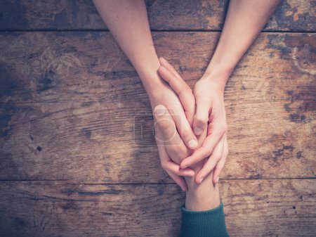 Photo for Close up on a man and a woman holding hands at a wooden table - Royalty Free Image