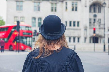 Photo pour Une jeune femme portant un chapeau melon et une robe de remise des diplômes marche dans les rues de Londres - image libre de droit