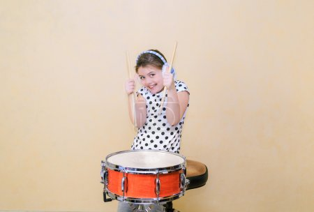 Photo pour Little happy joyful girl in motion sitting behind the snare drum and holding a sticks against Tuscan sun Venetian plaster wall background - image libre de droit