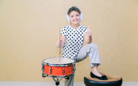 Photo pour Fashionable joyful pretty little girl standing and holding sticks behind a snare drum against old vintage yellow  wall background - image libre de droit