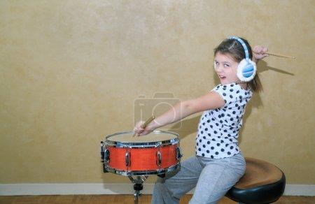 Photo pour Petite fille stylisée drôle active dans la pratique de mouvement sur le tambour de caisse claire dans la salle de studio sur le fond de mur de cru - image libre de droit