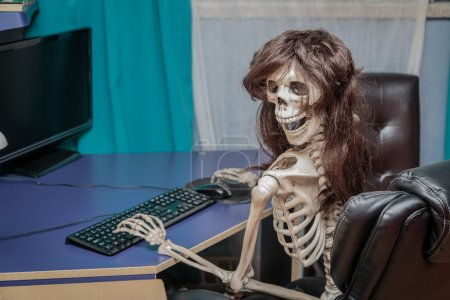 Joyful smiling skeleton in a wig sitting in chair behind the desktop computer