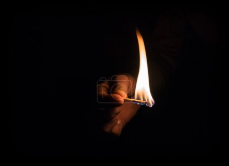 Hand holding burning matchstick in darkness