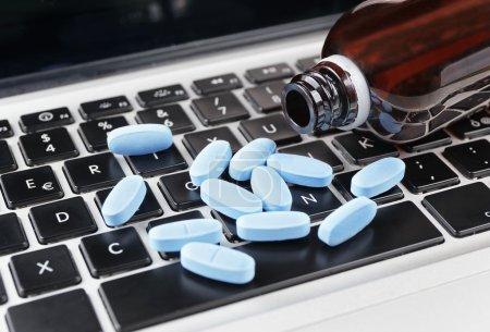 Photo pour Pilules gros plan sur le clavier de l'ordinateur, médecine de vente en ligne concept - image libre de droit