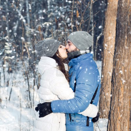 happy couple kissing in winter forest