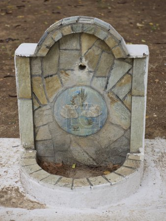 Traditional drinking water fountain in green park in Elefsina