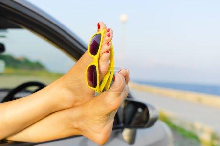 Photo pour Voyage vacances liberté plage concept. Jambes féminines par la fenêtre de la voiture . - image libre de droit