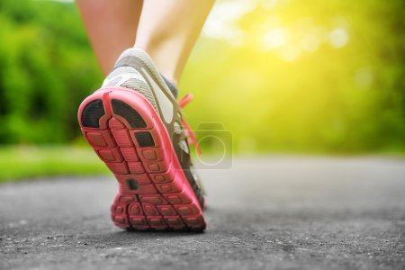 Photo for Womans legs in shoes on runner jogging in the park at sunset - Royalty Free Image