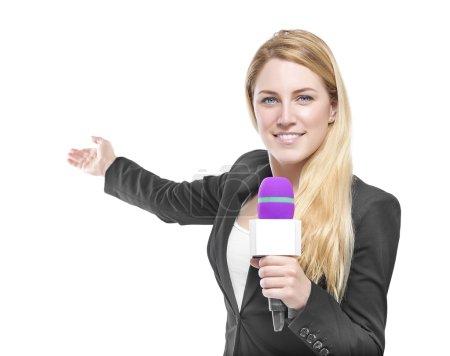 Photo pour Jolie présentatrice blonde tenant un microphone et pointant vers un objet. Isolé sur fond blanc . - image libre de droit