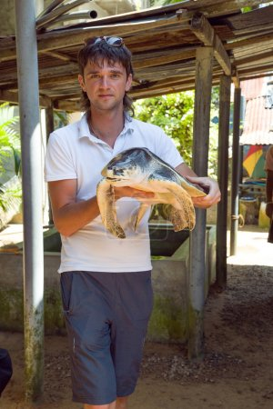 A young man with a big turtle