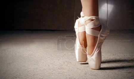 Photo for Feet of ballerina dancing in ballet shoes over a dark background - Royalty Free Image