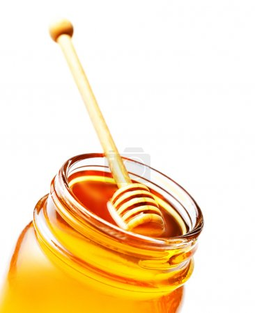 Honey in a glass jar with honey dipper