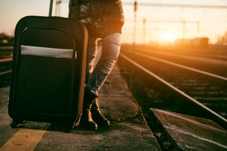Photo for Traveler woman with baggage on train station at sunset background - Royalty Free Image