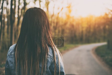 Photo for Brown hair woman on the road rear view - Royalty Free Image