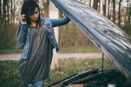 Photo pour Jeune femme caucasienne aux cheveux bruns sous le capot de sa voiture se décomposent - image libre de droit