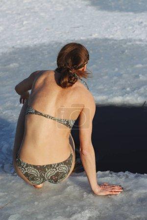 Photo pour Fête de l'épiphanie. Fille en maillot de bain se baignant dans le durcissement des trous de glace, récupération, une jeune femme plonge dans l'eau glacée d'un lac, Ukraine, Janvier - image libre de droit