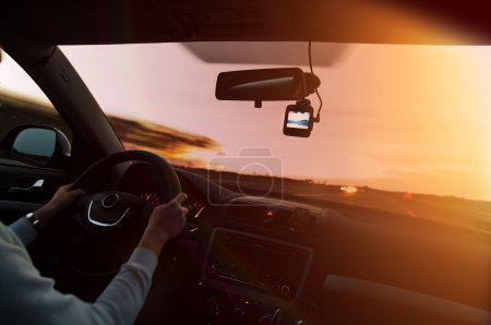 Driving at sunset with video recorder