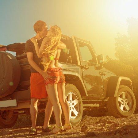 Photo pour Un couple baiser à côté d'une voiture 4 voies sur coucher de soleil - image libre de droit