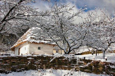 Photo pour Conte de fées maison authentique d'hiver avec murs blanchis à la chaux de clôture tissée - image libre de droit