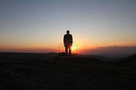 Foto de Un hombre está parado en la montaña y saluda al sol naciente - Imagen libre de derechos