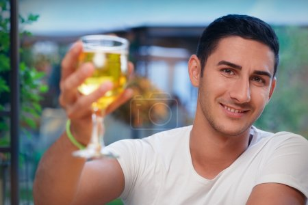 Portrait of a handsome man drinking and making a t...