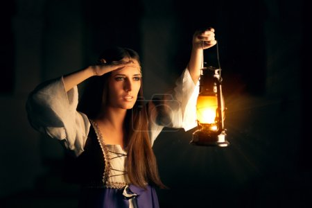 Photo for Portrait of woman wearing a vintage dress holding a lamp seeking in the dark - Royalty Free Image