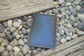 digital tablet device on stone and wooden walkway