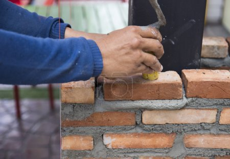 the worker is masoning the brick