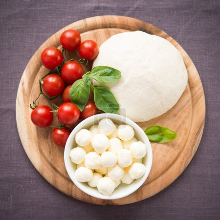 Ingredients for pizza margherita on wooden plate top view
