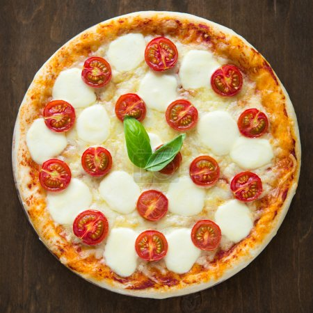Pizza Margherita on dark wooden background top view