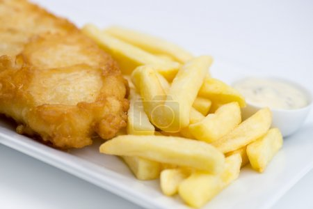 Closeup of battered fish and chips with tartar sauce on white