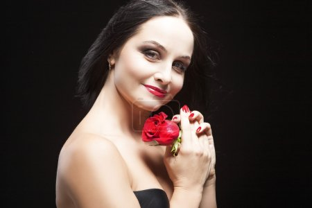 Portrait of Caucasian Brunette Female Posing With Rose Against Black Background.