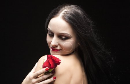 Sexy Sensual Brunette Woman Posing With red Flower in Studio Against Black