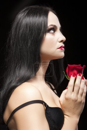 Portrait of Sensual Brunette with Red Flower Against Black Background.