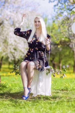 Sensual Blond Female Relaxing In Spring Forest on Swing.